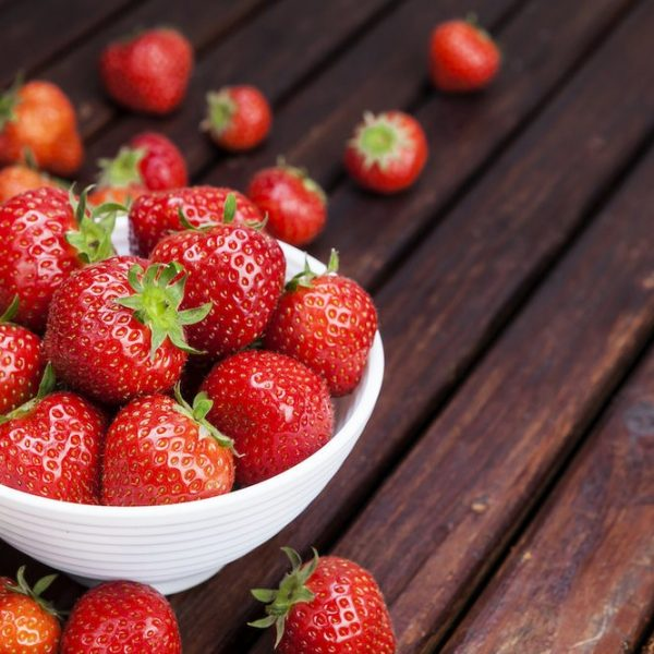 Strawberry in bowl on wooden table. Copy space